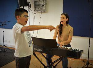 niño recibiendo clase de canto de maestra en academia musical TUTEMPO