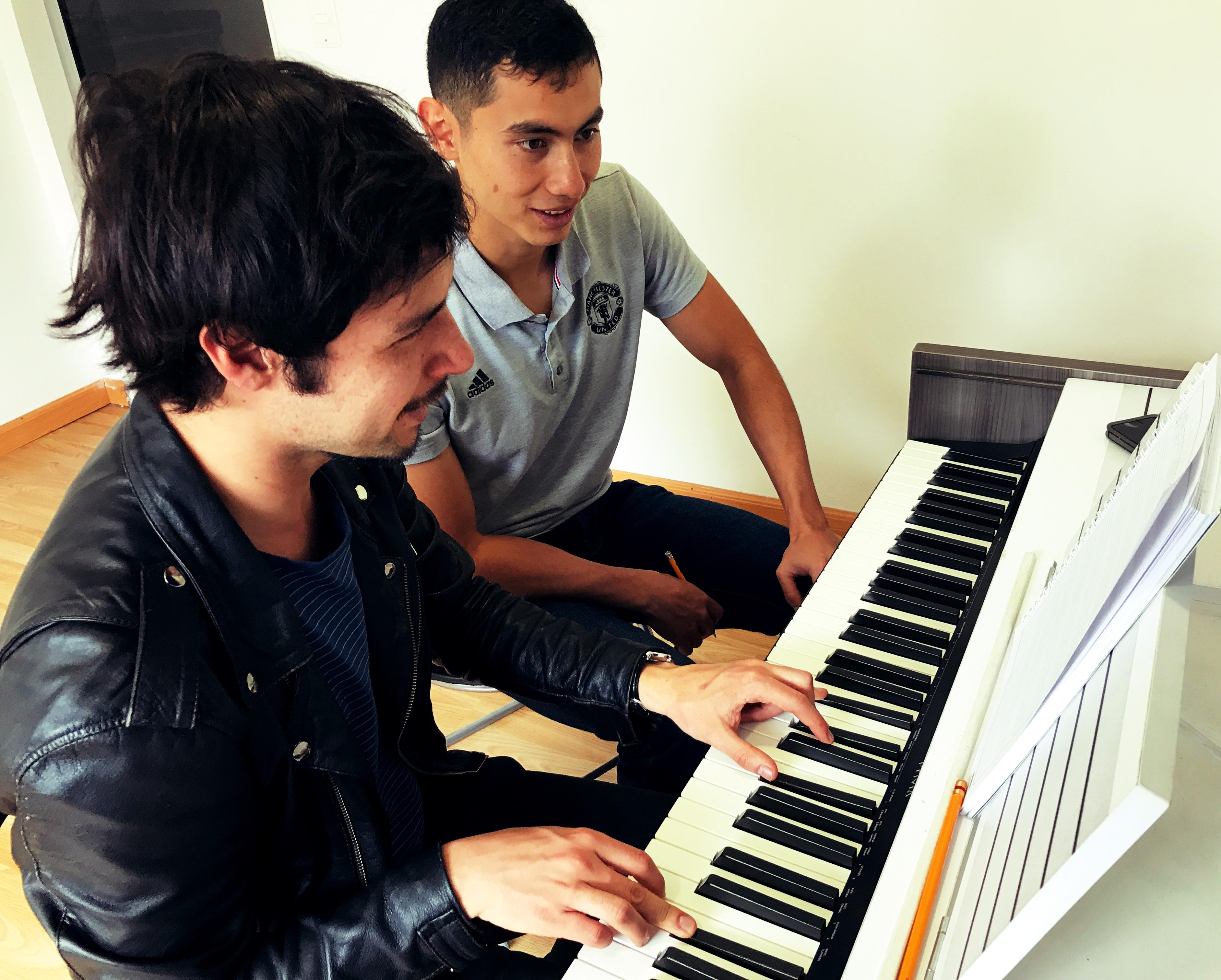 joven recibiendo clase de musica frente a teclado en academia musical TUTEMPO