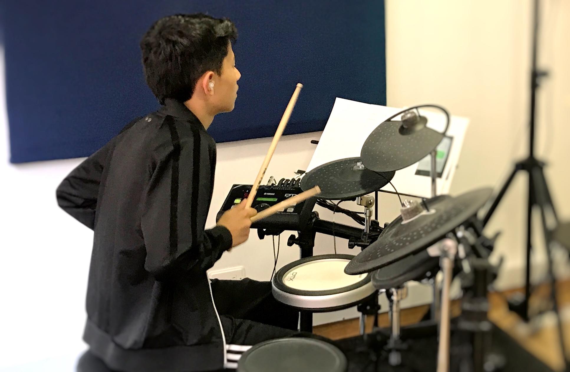 joven tocando batería en academia musical TUTEMPO