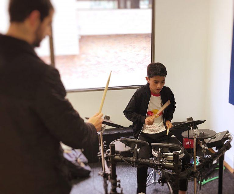joven recibiendo clase de batería en academia musical TUTEMPO