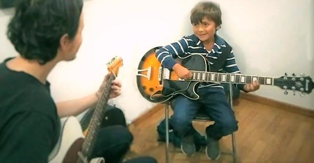 niño recibiendo clase de guitarra en academia musical TUTEMPO