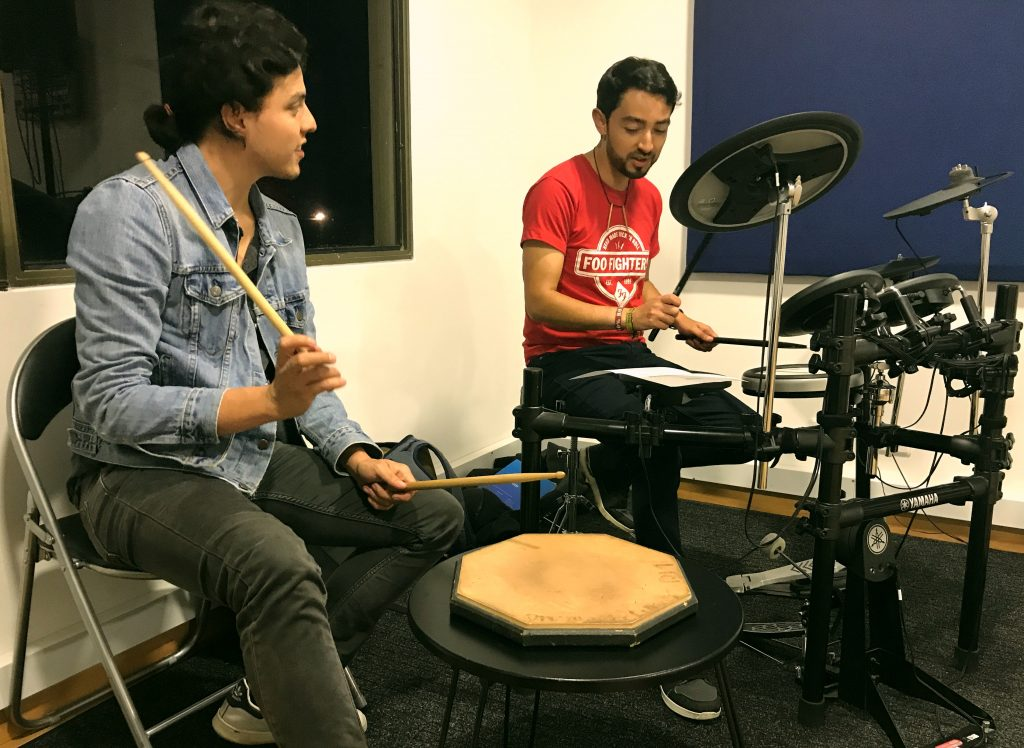 hombre recibiendo clase de batería en academia musical TUTEMPO