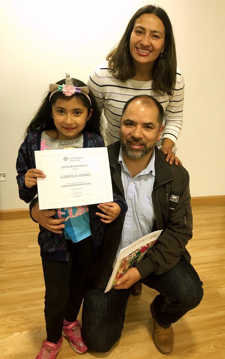 niña recibiendo certificado de curso junto a su familia en academia musical TUTEMPO