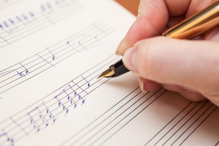persona escribiendo notas musicales en partitura