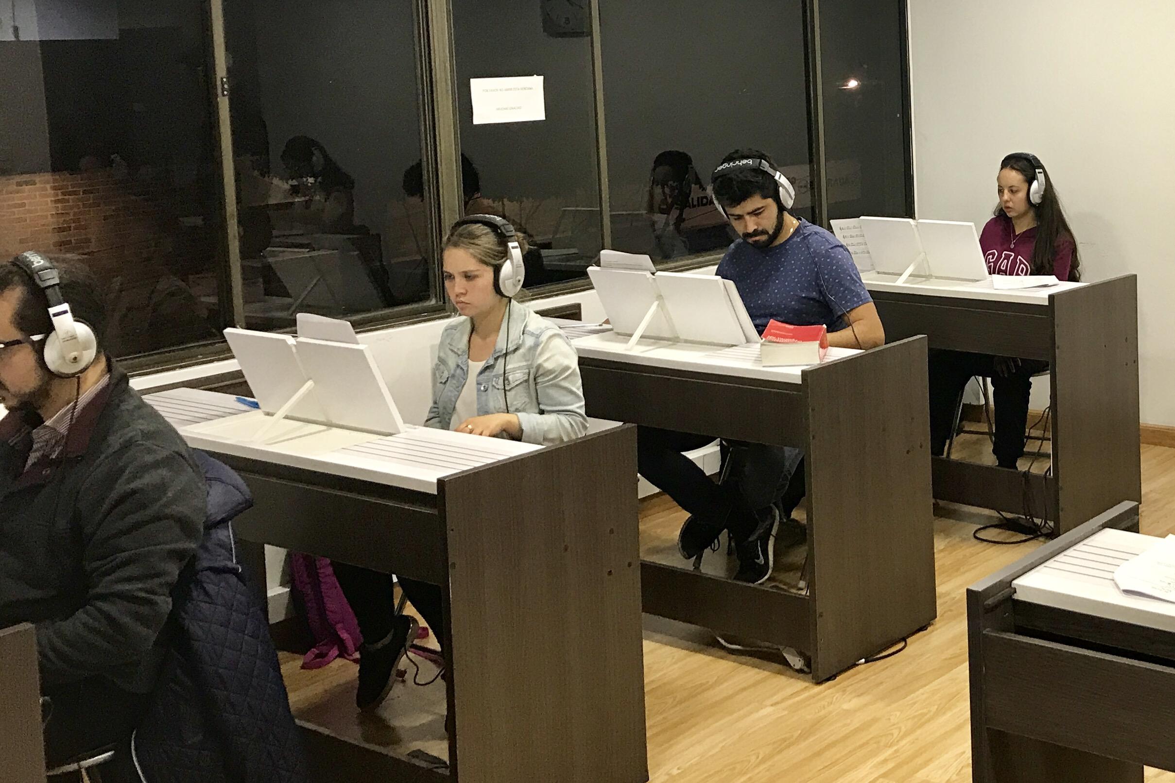 estudiantes de música frente a teclados en academia musical TUTEMPO