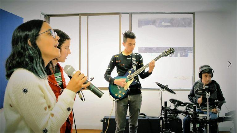jóvenes de grupo musical tocando guitarra y batería y cantando en la academia musical TUTEMPO