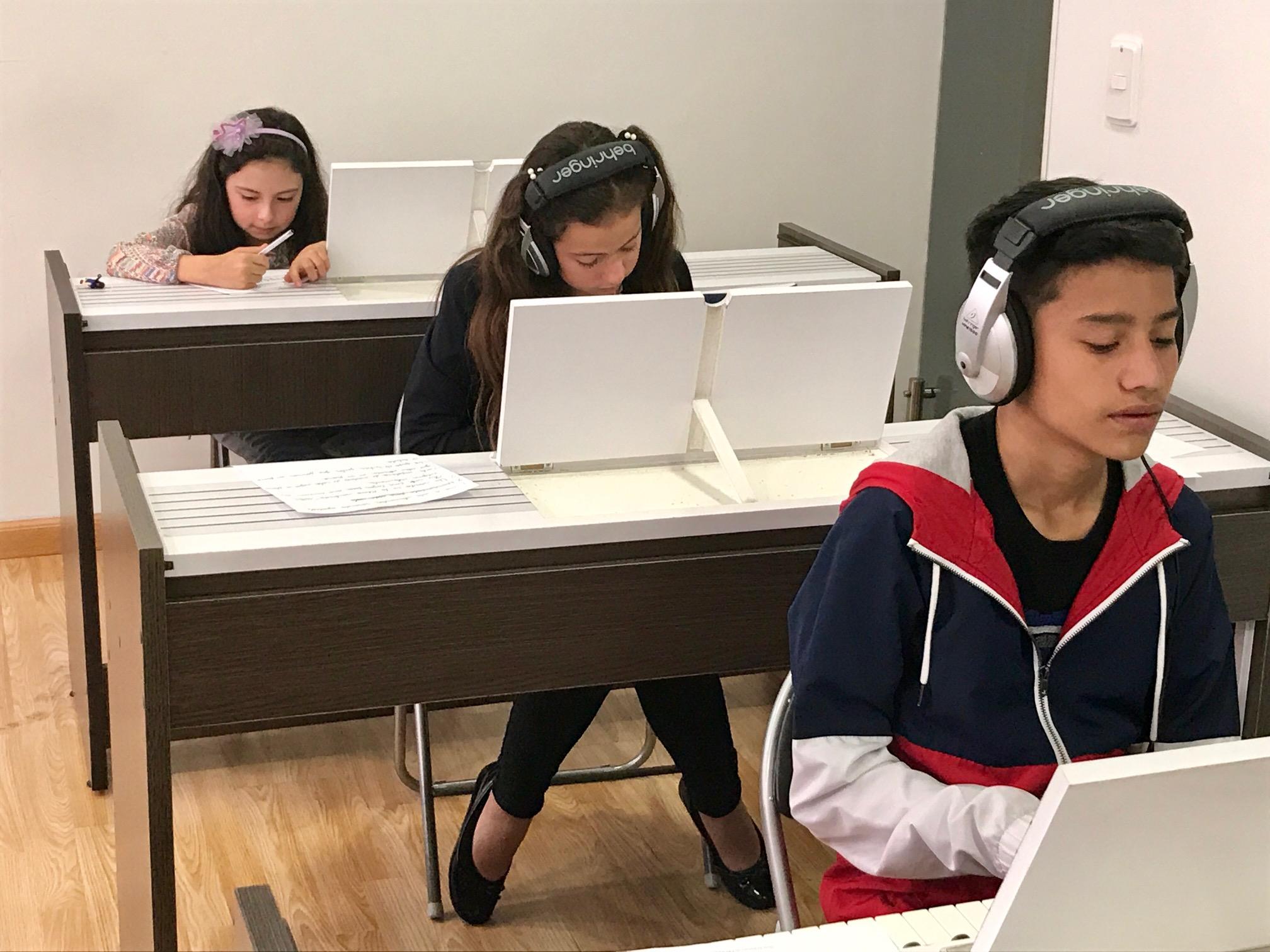 niños y jóvenes frente a teclados estudiando en academia musical TUTEMPO