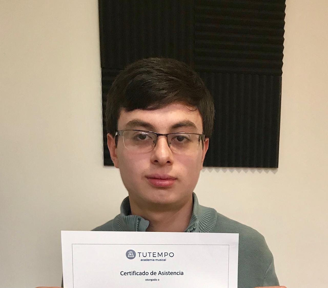 Juan Sebastián, estudiante de piano, obteniendo certificado en TUTEMPO academia musical