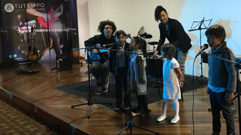 Niños cantando en concierto de estudiantes de TUTEMPO, acompañados de 2 profesores