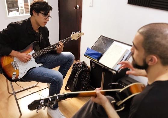 estudiante tomando clase de guitarra