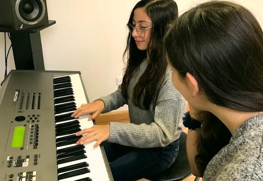 jovencita tomando clase de piano