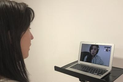 mujer frente a computador recibiendo clases de canto online