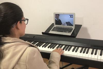 mujer tocando piano frente a computador recibiendo clases online